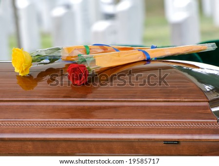 Horizontal photo of yellow and red rose on casket at Arlington National Cemetery with gravestones in background