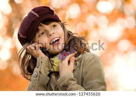 horizontal photo,  stylish beautiful little girl hold  mobile phone and gladness talk - stock photo