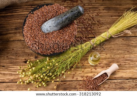 Horizontal photo with a bunch of flax plants with dried blooms bonded by natural cord placed on old wooden board and with burlap around which is near to bottle with flax oil and heap of flax seeds. - stock photo