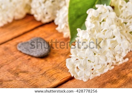 Horizontal photo with several flowers of lilac. Single green leaf on lilac blooms. White lilac blooms. Flowers with heart shaped stone placed on wooden board. Grey stone next to flowers. - stock photo