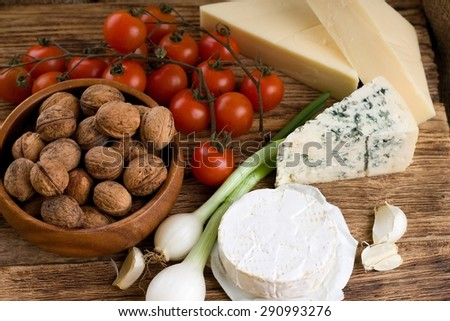 Horizontal photo with three kinds of cheese as eidam, camembert and danish blue niva and various fruit and vegetable as walnuts, tomatoes, garlic and onion all on wooden board. - stock photo
