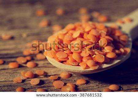 Horizontal photo with vintage filter of wooden spoon on wooden board with small heap of red lentils with few pieces spilled around.  - stock photo