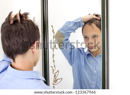 horizontal photograph of a young boy combing his hair while looking at himself in a mirror - stock photo
