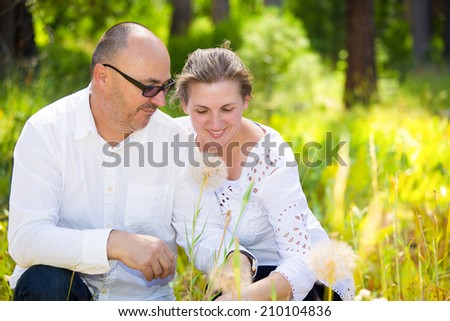 Horizontal Portrait happy, smiling mature couple, husband and wife hugging each other, relaxing on a summer sunny day in park. Positive human face expressions, emotions, feelings, life perception - stock photo