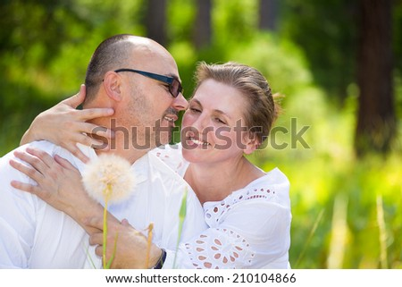 Horizontal Portrait happy, smiling mature couple, husband and wife hugging each other, relaxing on a summer sunny day in park. Positive human face expressions, emotions, feelings, life perception