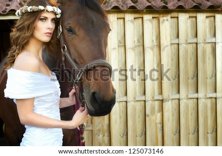 Horizontal portrait of a beautiful bride and horse - stock photo