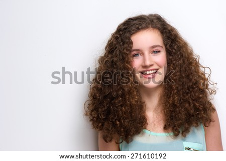 Horizontal portrait of a cheerful teenage girl laughing on white background - stock photo