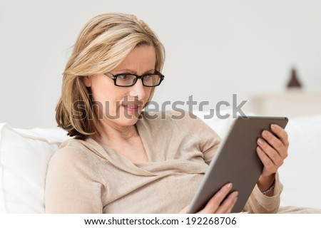 Horizontal portrait of a middle-aged blond Caucasian woman wearing black frame eyeglasses while sitting comfortably on a sofa using a large tablet PC - stock photo