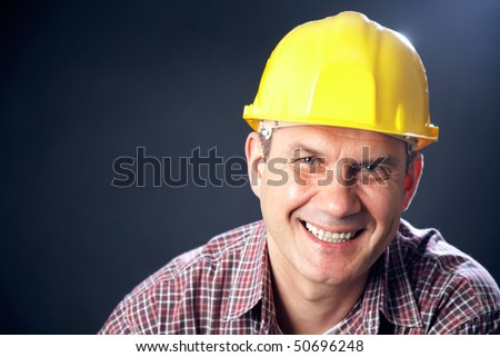 horizontal portrait of a smiling handsome man-builder on a dark background - stock photo