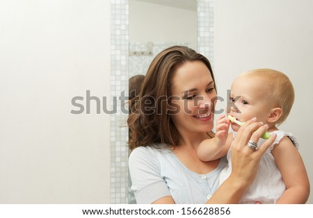Horizontal portrait of a smiling mother teaching cute baby how to brush teeth with toothbrush - stock photo