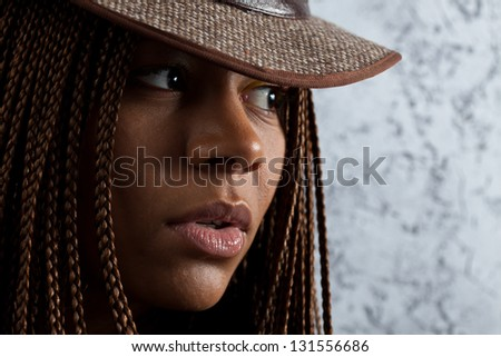horizontal portrait of a young black woman in hat - stock photo