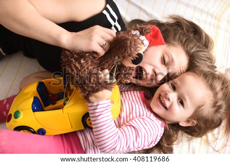 horizontal portrait of a young mother laying with her little daughter and car and teddy bear toys in their hands, making faces, laughing and looking happy - stock photo