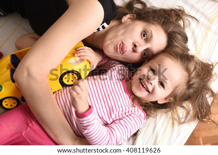 horizontal portrait of a young mother laying with her little daughter in pajamas and car toy, making faces, laughing and looking happy - stock photo
