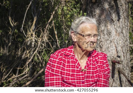 horizontal portrait of an elderly woman from the chest up with grey hair and wearing glass in a bright pink checkered dress. - stock photo