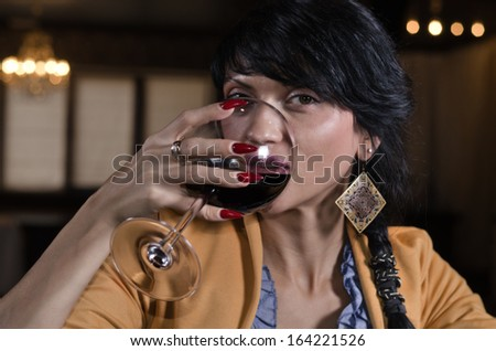 Horizontal portrait of an elegant beautiful young brunette woman drinking red wine from a saucer glass in a bar - stock photo