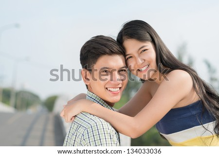 Horizontal portrait of an embracing couple smiling and looking at camera