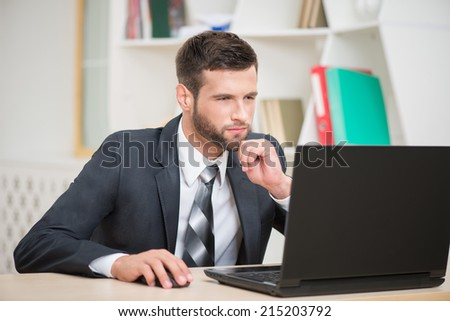 Horizontal portrait of handsome businessman sitting at the table and attentively working and looking at laptop in office background  - stock photo
