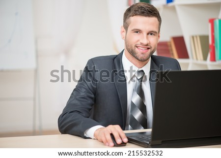 Horizontal portrait of handsome businessman sitting at the table working with laptop looking at the camera and happy smiling in office background  - stock photo