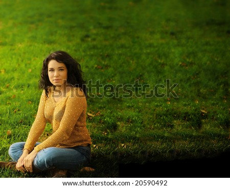Horizontal portrait of hispanic woman against green grass with lots of copy space - stock photo