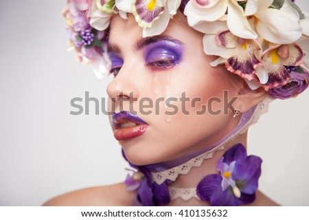 horizontal portrait of Sad young woman with flowers on head and makeup in purple tones crying in studio on grey background