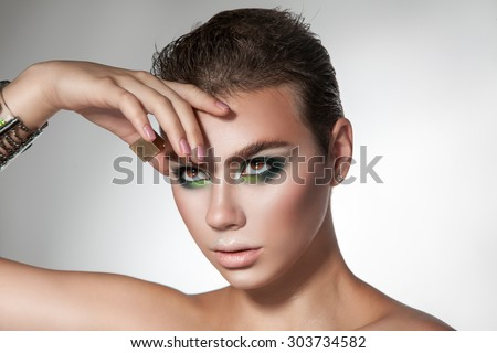 horizontal portrait of young beauty girl with green colors makeup and short hairstyle. studio shot. horizontal. grey background - stock photo