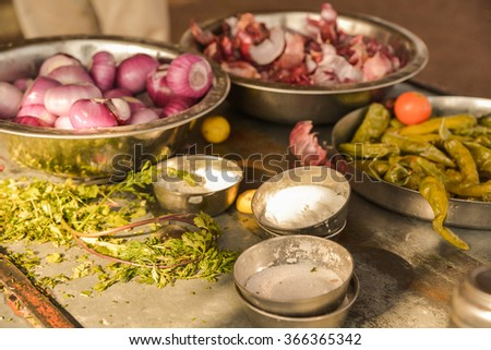 Horizontal, selective focus shot of red onions, red tomatoes, green chilis, cilantro, lemon, and salt ready for an indian meal prep. This was shot at a road side stand in Jodhpur, India.  - stock photo