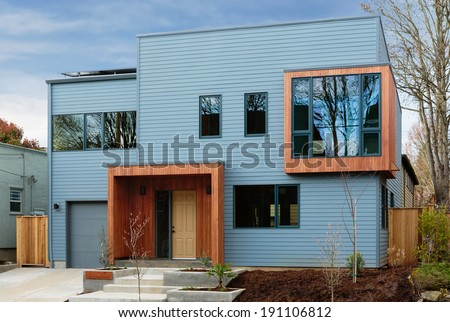 Horizontal shot of a modern, upscale home with blue sky/with metal and wood details and window reflections - stock photo