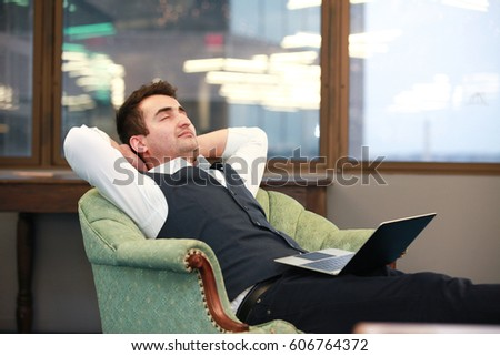 Horizontal shot of adult man sitting with eyes closed in office in Arlington city, Virginia.