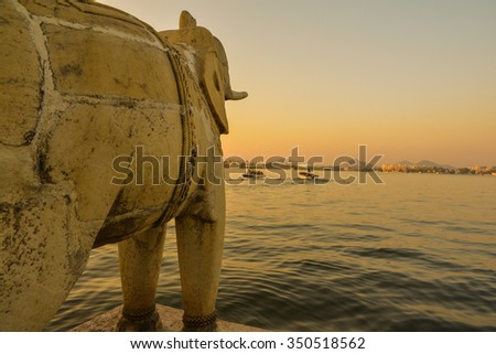 Horizontal shot of an elephant statue looking out from Jag Mandir Island at sunset over the lake. This was shot on Lake Pichola in Udaipur, India.  - stock photo