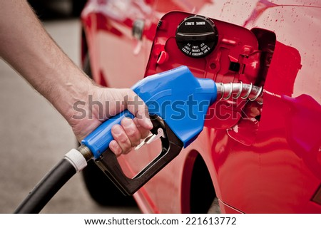 Horizontal Shot Of Blue Gas Nozzle In Red Car Tank/  Pumping Gas - stock photo