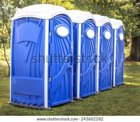 Horizontal Shot Of Blue Port Potties Or Portable Toilets - stock photo