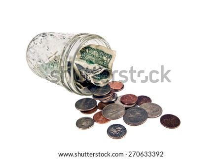 Horizontal shot of coins spilling from coin jar/ Coins Spilled From Coin Jar - stock photo