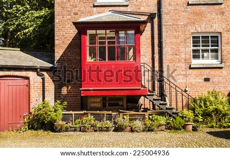 Horizontal shot of  old courtyard with redbrick house and iron steps leading to a red porch - stock photo
