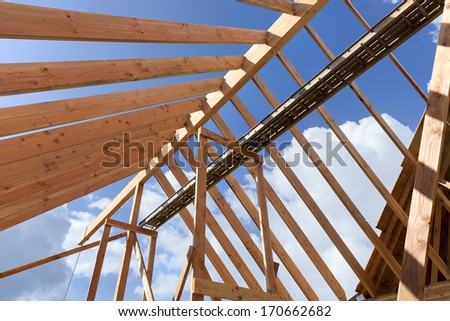 Horizontal shot of post and beam roof construction with view of sky/New Home construction with exposed beams and blue sky background - stock photo