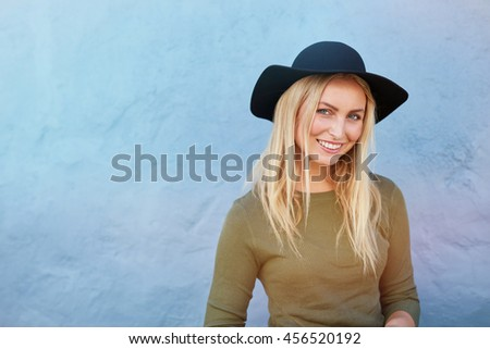 Horizontal shot of smiling young female wearing hat looking at camera and smiling. Attractive young female model standing in front of a blue wall. - stock photo
