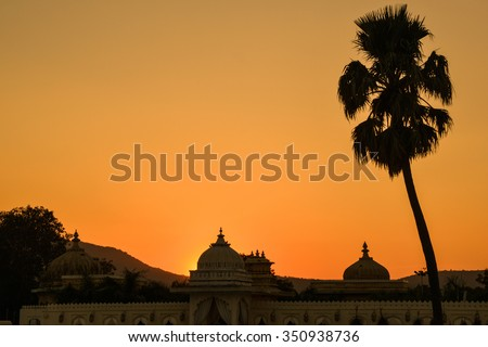 Horizontal, silhouetted shot of Jag Mandir Palace at sunset with palm trees and hills. This was shot on Jag Mandir Island on Lake Pichola in Udaipur, India.  - stock photo