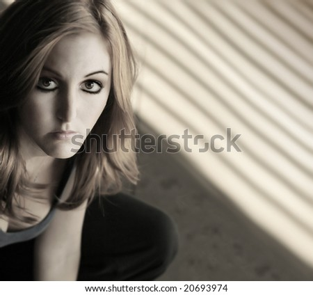 Horizontal stylized close-up portrait of a serious young woman near window with a lots of copy space - stock photo