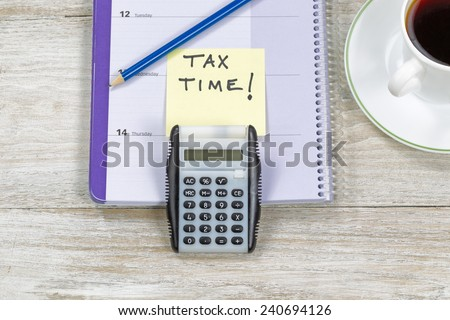 Horizontal top view of an office wooden desktop with small calendar, calculator, coffee and sharpen blue pencil with reminder of doing Tax Returns.  - stock photo