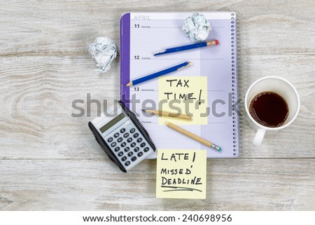 Horizontal top view of an office wooden desktop with small calendar, calculator, coffee, wadded paper, and broken pencils, showing teeth marks, during tax preparation.   - stock photo