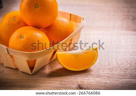 horizontal version oranges in wicker basket on wooden board  - stock photo