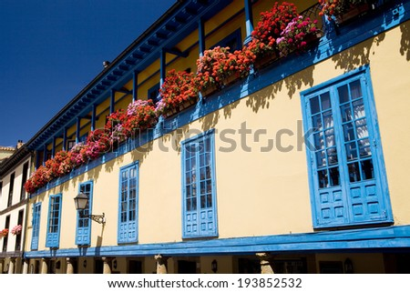 Horizontal view of a facade with blue windows and a lot of flowers in Oviedo, Asturias, Spain. Facade with flowers. - stock photo