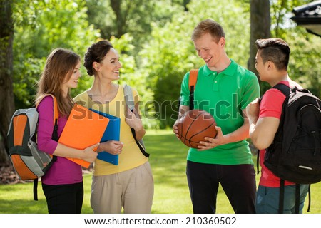 Horizontal view of a group of students talking outdoors - stock photo