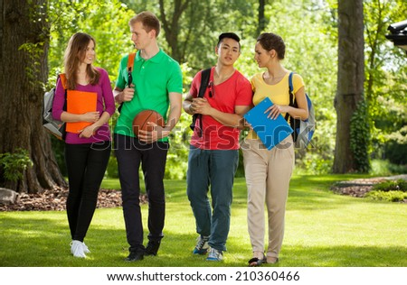 Horizontal view of a happy college students outdoors - stock photo