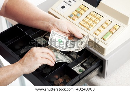 Horizontal view of an open cash register drawer asa a cashier makes change. - stock photo