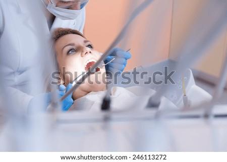 Horizontal view of dentistry examining patient's teeth - stock photo