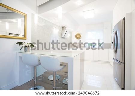 Horizontal view of designer white kitchen interior - stock photo