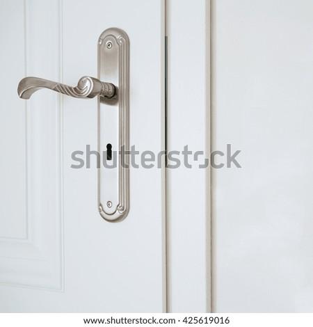 Horizontal view of door-handle in white door - stock photo