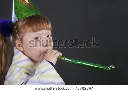Horizontal view of little girl playfully blowing noisemakers a birthday party - stock photo