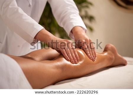 Horizontal view of masseur massaging female calf - stock photo
