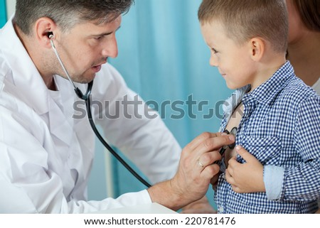 Horizontal view of pediatrician listening preschooler heart - stock photo